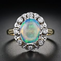Vintage Style Opal Diamond Ring - This lovely opal ring was recently crafted in England in a classic vintage style. The oval opal glows with a hypnotic palette of blues and greens with flashes of orange and yellow and is wreathed in a white gold open work diamond setting atop an 18k yellow gold shank and gallery.