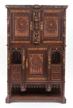 A GOTHIC REVIVAL CARVED WOOD AND PARCEL-GILT CUPBOARD. 19th century.
