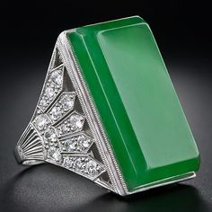 Colossal Natural Jade Art Deco Ring - The beveled rectangular gemstone is exquisitely presented in in a gorgeous platinum Art Deco mounting between a pair of sparkling diamond-set fans. Very fine milgraining and a gracefully scrolled open work gallery complete the look. Burmese Jade.