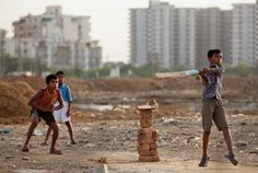 Children in a slum near the center of Gurgaon, India play cricket early Wendesday evening. The slum is home to many migrant domestic workers who hail from areas like Bengal. They come to work as domestic helpers for people in the high-rise apartments and send their paychecks back to family at home. (photo by Matt Masin)