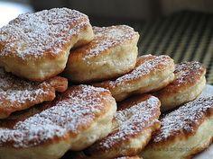 1/2 kg mąki pszennej 50 g świeżych drożdży (pół tradycyjnego opakowania) lub 25 g suchych szczypta soli 1 - 2 łyżki cukru 1,5 szklanki letniego mleka 1 jajko Mąkę przesiać, dodać szczyptę soli, wymieszać. Do wgłębienia pokruszyć świeże drożdże, zasypać cukrem, zalać 1/2 szklanki letniego mleka. Odstawić na 10-15 minut. Po tym czasie dolać resztę mleka, jajko i wymieszać. Odstawić na 1-1,5h do wyrośnięcia. Ciasto nabierać łyżką, za każdym razem maczaną uprzednio w gorącej wodzie. Smażyć na…