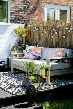 Swoonworthy Boho Garden Makeover featuring reed screening, outdoor sofa and outdoor rug