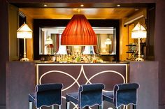 This elegant bar is backed with a large mirror, and includes velvet blue stool seating, a pair of lamps, and a large orange fabric pendant light.