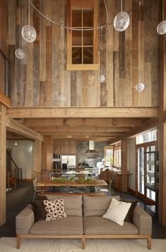 An open floor plan and abundant reclaimed wood make the interior of this cabin feel warm and inviting    (via Robert Hawkins)