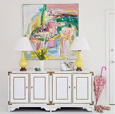 I love this dresser (look at the hardware on it), the painting, and the yellow lamps.