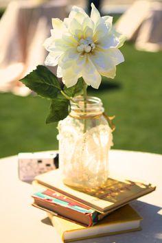 wedding centerpiece: old books + doily mason jar + twine + flowers + throw away cameras