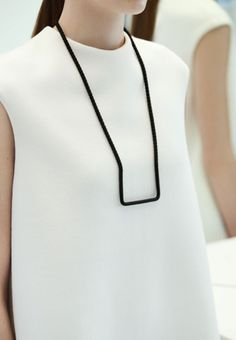 black necklase from Cos in minimal design looks great with a white dress or a top