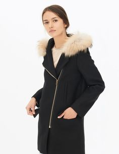 Sandro long coat with long sleeves and a round collar. 100% wool. Two flap patch pockets. Diagonal zip fastening. Detachable fur on the hood. A basic design with a new twist, making it a wardrobe must-have. Model is wearing a size 1.