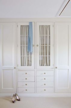built in drawers/shelves with glass face and linen curtains on inside. Nice look