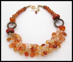 Rich Fall tones....4 strands of brio cut Carnelian nuggets are woven thru old, handmade Amber resin beads from Morocco and Nepal. Very old,