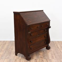 This empire inspired secretary desk is featured in a solid wood with a rustic dark cherry finish. This desk is in great condition with 5 drawers, a drop down desk and carved curved details. Perfect for storing paperwork and files! #neoclassical #desks #secretarydesk #sandiegovintage #vintagefurniture
