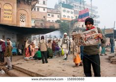 VARANASI, INDIA - JANUARY 4: Young man reads a newspaper in the crowd of hindu people at the morning on January 4 2013. The 2,525 km river rises in Indian state Uttarakhand & flows into Bangladesh - stock photo