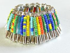 Make a bracelet out of safety pins and beads! Safety Pin Bracelet, Safety Pin Jewelry, Safety Pin Earrings, Beaded Statement Necklace, Beaded Jewelry, Beaded Bracelets, Vintage High Chairs, Christmas Tree Beads, Bead Jewelry