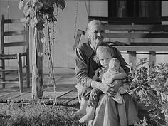 Mountain woman and grandchild sitting on the porch of their home up Frozen Creek, Breathitt County, Kentucky 8c13882u