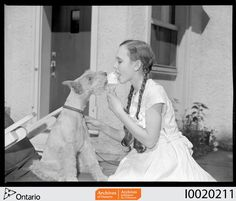 Archives of Ontario, Pianist Patsy Parr eating ice cream with a dog Date: August 1949 Creator: Gilbert A.
