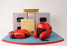 Kickboxing by Charm City Cakes - Sculpted kickboxing helmet and gloves sit next to boards ready to be broken on top of cinder blocks.