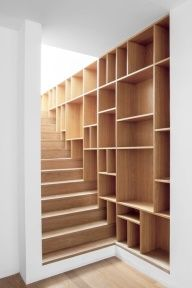 Bookcases seamlessly blend into stairs to make a book-lined wall. Inventive use of space, functional. Imagine what this space would look like when it ran out space from books on every shelf!