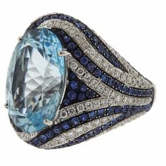 An 18k white gold ring set with a blue topaz (18mm x 13mm) 1.53ctw of G/VS diamonds and sapphires. DESIGNER: Asprey MATERIAL: 18k Gold GEMSTONE: Diamond, Topaz DIMENSIONS: Size 7, Top is 23mm wide. WE