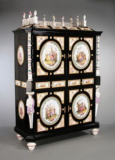 This German Renaissance Revival cabinet is lavishly decorated with porcelain plaques, figures and caryatids and is fitted on the interior with porcelain figures, columns and drawer fronts. Each plaque is painted with a different 18th-century country scene