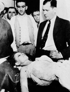 Bonnie Parker lays in the morgue at Arcadia, Louisiana after being shot to death on a nearby country road with her bank robber partner, Clyde Barrow (May Looking on at right is Bill Decker, Chief Deputy Sheriff of Dallas County, Texas.