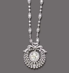A BELLE EPOQUE DIAMOND AND COLORED DIAMOND NECKLACE   Centering upon an independent old European-cut yellow diamond, within an old European-cut diamond frame, suspended from a rose, single and old European-cut diamond wreath garland, to the similarly-set diamond ribbon bow and navette-shaped link neckchain, enhanced by diamond collets, mounted in platinum, circa 1905, 21 ins.