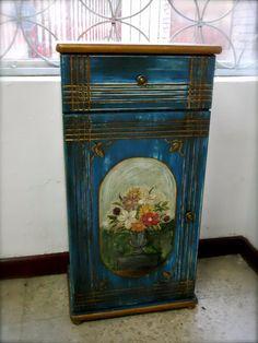 Transformación de un viejo armarito de baño en una mesita de noche, envejecida en azul y oro, y decorada con dibujo floral a mano alzada. Interior forrado.