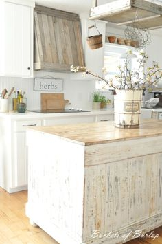 Farmhouse kitchen with reclaimed wooden vent hood. Vintage island and painted white countertops. Pear blossoms in a vintage ice cream bucket