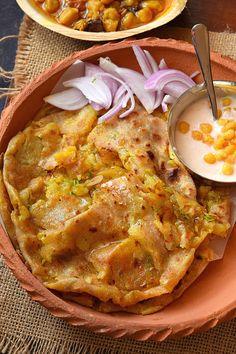 A clay plate having Aloo Pyaz Naan Dhaba style with boondi raita and punjabi chole