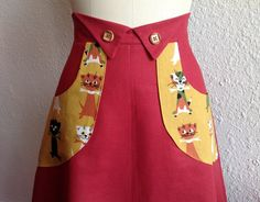 This sweet skirt is made out of rusty red linen, cut in an a-line shape with a high waistband accented by cute detailing at the center front with wooden buttons. The skirt has mustard yellow pockets printed with cats in olive, white, orange and black. The skirt is lined and zips up the back.  Size 8 Measures 29 around the high waist 39 around the hips 25 long from center front waist  Hand wash and air dry