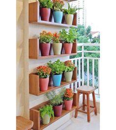 Jardim vertical: o colorido ficou por conta dos vasos, que ficam dispostos harmonicamente em prateleiras de madeira.