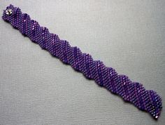 The Flat Cellini (chel-ee-nee) spiral is the result of using beads that are in different sizes to give you the graduated spiral. The Cellini spiral came about from a technique taught by Virginia Blakelock and Carol Perrenoud who are considered seed bead masters. They named the stitch after a 16th century Italian Sculptor named Benevento Cellini. After the tubular Cellini was born, the flat Cellini spiral stitch was developed also.
