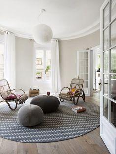 un salon scandinave blanc avec deux poufs gris tricotés et un tapis rond et gris
