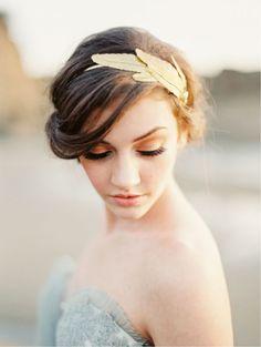 Si vous préférez une allure plus sobre, que pensez-vous de cette coiffure ? Les cheveux sont attachés en chignon lâche, avec quelques mèches qui reviennent jusque sur les yeux. La mariée porte un headband doré avec de fausses plumes en métal de la même teinte que l'anneau. Une couleur royale qui se démarque bien sur des cheveux bruns comme ici. Ce bijou de tête n'est pas clinquant et apporte juste ce qu'il faut de glamour à la coiffure.