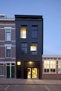 The Black Pearl Residence, Studio Rolf.fr i.s.m. Zecc Architecten. Residence and workshop, Rotterdam. Facade of abandoned building painted in black oil lacquer, new white steel reveals puncture the facade creating a kind of optical illusion of past and present.
