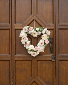 A floral heart-shaped wreath of hydrangeas, roses, and peonies decorated the doors of this rustic wedding in the English countryside.