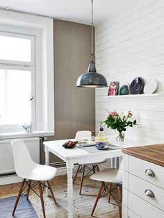 I like how the traditional painted table has been paired with contemporary chairs and modern kitchen cabinetry.