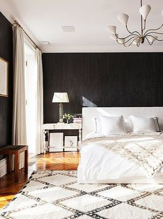 Among the dark walls, the airy white bed seems to float in the center of the bedroom atop a vintage Beni Ourain Moroccan rug.