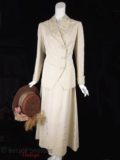 Edwardian walking suit in cream faille with ornate embroidery. Fully lined jacket features shawl collar and asymmetrical closure with three covered buttons. The back has an embroidered flap echoed on