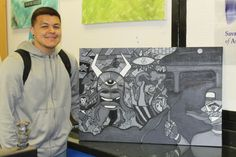 """Ames High School senior Siriaco Garcia shows one of his recent paintings, """"Siricaso Guenicia."""" Inspired by Pablo Piccaso's """"Guernica,"""" Garcia's acrylic painting includes stories from his family and his life growing up in a Texas border town. Photo by Melissa Erickson/Ames Tribune"""