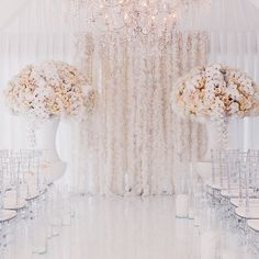 Add texture to an all-white #wedding with a feather curtain for an extra element of visual interest and dimension. Not to mention, the muted pastel #floral arrangements with feather accents are a beautiful bonus to this #ceremony space! Instagram repost: