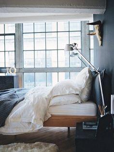 Un piso en Londres con un diseño masculino. En el dormitorio, colores oscuros, una pieza de taxidermia y el toque metálico con las dos lámparas #Tolomeo de @artemideworld