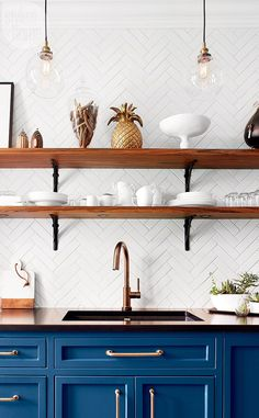 A trio of industrial-style pendant lights and open shelves with iron brackets reflect all the hallmarks of a French bistro. To keep everything neat, homeowner Dominique Tremblay displays only her white dishware.