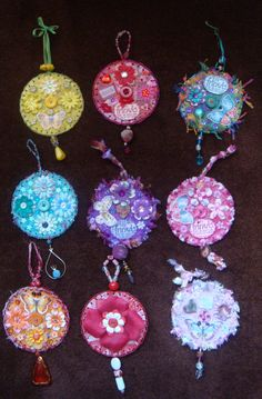 These are a bunch of CDs I've altered to sell in a forthcoming craft fair in June. I've glued scraps of text, music score and maps to cover the CDs and then covered over with coloured tissue paper. I then used my cropodile to punch holes around the CD and blanket stitched with different fibres. I used an assortment of beads for some of the hangers and drops and have stuck paper, silk flowers and butterflies and other embelishments to each CD to decorate.