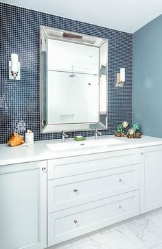 Light gray bath vanity cabinets donning glass pulls sit on marble floor tiles and are fitted with a white quartz countertop holding a white trough sink with two polished nickel faucets fixed beneath a Restoration Hardware Venetian Beaded Mirror flanked by nickel and white glass sconces mounted on blue grid backsplash tiles.