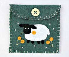 Green felt coin purse with sheep and flowers, contrasting lining, blanket stitched edges and button fastening. 9cm x 9cm / 3.5 x 3.5 inches  For