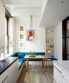 """This is where our family lives,"" says Beeber of the inspired breakfast nook that's neatly tucked into a corner of the kitchen. The brightly hued bench is upholstered in a luxurious (and durable) Moore & Giles leather; the Hem table is topped with a Kalmar fixture found at the Bright Group, and vintage lithographs picked up at auction embellish the wall. ""My two-year-old son loves sitting on the banquette and looking out the window at the endless construction on Astor Place,"" she says."