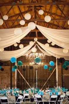 Barn Wedding Reception with floating balloons and sheer drapery hung across the rafters