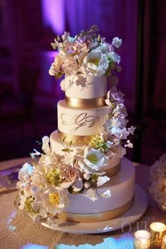 A spiral cascade of sugar flowers, gilded icing bands and a confectionery monogram. Photo: Christian Oth www.weddingcakes.com