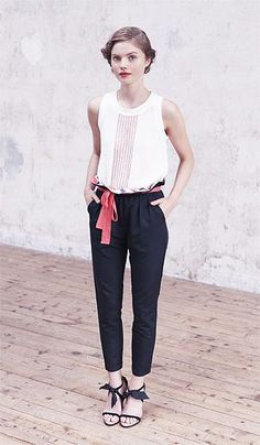 white blouse with pleated front tucked into black carrot trousers