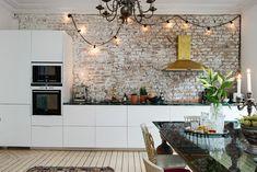 Cocina con armarios minimalistas blancos y pared de ladrillo. ¡Campana extractora con acabado de cobre!